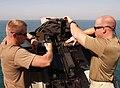 US Navy 091112-N-6156A-002 Operations Specialist 2nd Class Joseph Goodfellow nd Postal Clerk 2nd Class Christopher Fish perform daily function checks on a .50 caliber dual mount machine gun.jpg