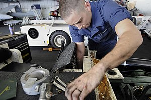 US Navy 120130-N-RG587-162 A Sailor bolts the console cover onto a jet tow tractor.jpg
