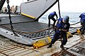 US Navy 120202-N-WV964-073 Seaman Brandon Snook removes chains from a landing craft utility in the well deck of the forward-deployed amphibious doc.jpg