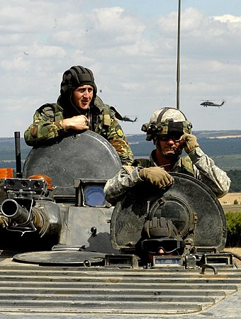 Two Bulgarian Army soldiers man the driver's and gunner's stations, while a US Army soldier occupies the commander's position of a Bulgarian BMP-1 IFV.