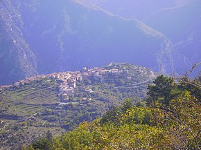 Photo looking down a town situated on a high plateau amid tree-covered mountains