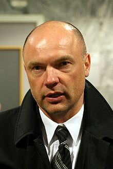 A photograph of a man at a press interview. He is wearing a black coat and a white shirt. The man is in the middle of a discussion with a person not seen in the image.