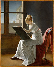 An oil painting of a young woman dressed in a flowing, white dress sitting on a chair with a red drape. An easel rests on her knees and she is evidently drawing, she is gazing directly at the observer.