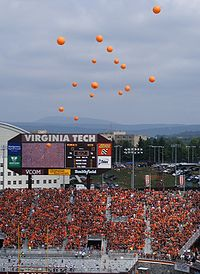 Orange balloons rising above Lane Stadium, with everyone in the stands wearing maroon or orange, and the stadium scoreboard in the background.