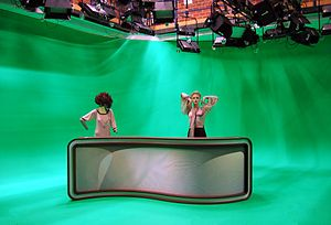 Chroma key - Virtual television studio with green-screen technique. The high amount of contrast between different parts of the screen is not ideal (see even lighting). Green reflections from the desk would create undesirable artifacts.