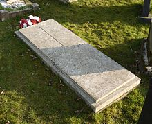 A granite headstone with a cross inscribed on it and a bunch of red and white flowers next to it, among many other gravestones