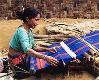 Une femme du Bangladesh tissant. Le travail textile fut longtemps associé à un rôle féminin dans bien des cultures.  illustration traduite de l'article (es)Mujer