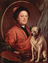 A man wearing a red robe and a black hat in a mirror. A small yellow dog with a black nose and ears stands beside the mirror.