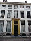 foto van Gepleisterde gevel met rechte getande kroonlijst, waarachter een ouder huis met zadeldak