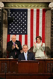 "Pelosi (right) with Vice President Dick Cheney behind President George W. Bush at the 2007 State of the Union Address making history as the first woman to sit behind the podium at such an address. President Bush acknowledged this by beginning his speech with the words, ""Tonight, I have a high privilege and distinct honor of my own — as the first President to begin the State of the Union message with these words: Madam Speaker."""