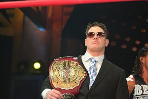 A white male wearing sunglasses and a black suit standing in a wrestling ring while holding a red leather championship belt