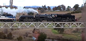 Restored steam locomotive no. 6029 hauling a load test train over the Queanbeyan River bridge