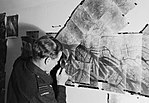 A Canadian photographic reconnaissance pilot examining a mosaic of Hamburg docks at Benson, Oxfordshire, August 1943. CH10865.jpg