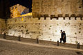 A Haredi couple walk hastily around the Towe of David late at night..jpg