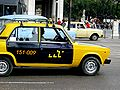 A full-sized Cuban Taxi driving down the street.jpg