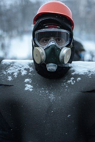 A protester wearing breathing gas mask, helmet and an improvised armor. Clashes between protesters and interior troops persist. Euromaidan Protests.jpg