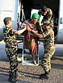 A rescued old woman being assisted by the Nepalese Armed Forces Personnel while alighting from a Mi-17 helicopter.jpg