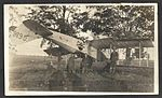 Aircraft C636, crashed upside down between two trees with three men standing in front of it. The aircraft bears the skull-and-crossbones insignia of 90 C.T.S., based at Camp Rathbun, one of the Royal (8512946263).jpg