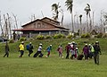 Aircrewman leads residents to an MH-60s Sea Hawk helicopter for evacuation. (37284282466).jpg