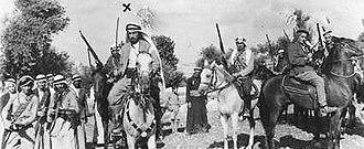 "Abd al-Rahim al-Hajj Muhammad - Al-Hajj Muhammad on horseback (beneath the ""x"" mark) with his fasa'il outside Kafr Sur. To his left on the brown horse is commander Abd al-Rahman al-Hattab and behind and to al-Hattab's left is Maarouf Saad, a volunteer and future parliamentarian of Sidon, Lebanon"