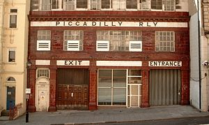 "Side elevation of station with the typical red-tiled facade. A pale tiled band with the words ""Piccadilly Railway"" runs across the top of the second storey and ""Exit"" and ""Entrance"" are displayed above shuttered doorways."