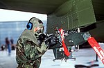 An airman wearing biological-chemical protective gear makes an adjustment to a bomb rack mounted on an A-10 Thunderbolt aircraft during the combat readiness competition Sabre Spirit '88 DF-ST-89-09059.jpg
