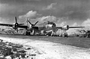 Black and white photo of a four engined propeller aircraft sitting on tarmac. Scaffolding has been erected near the nose of the aircraft and men are working on equipment nearby. The tail of another aircraft is visible to the right of the photo and buildings are visible behind the main aircraft.