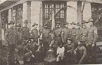 Balangiga massacre - American soldiers in Calbayog, Samar pose with a church bell taken from Balangiga as war trophy.