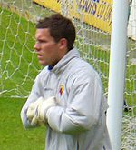 A man in a grey football shirt and goalkeeping gloves standing on a playing pitch in front of a goal.