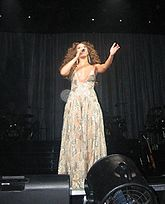 A woman sings on stage. She wears a long transparent dress while she holds her left arm open.