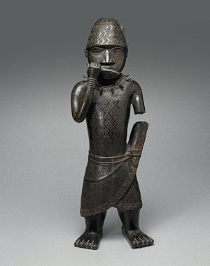 Benin ancestral altars - This figure of a hornblower, from the collection of the Brooklyn Museum, probably stood on an altar dedicated to a deceased king, or oba. His conical hat and elaborately wrapped skirt with a projection on the left side all indicate that he is a court official. The necklace of leopard's teeth was worn only by warriors. The horn this figure once held is believed to have been a type called an erere, blown during ceremonial sacrifices. A motif on the figure's kilt depicting an elephant, whose trunk ends in a human right hand, identifies this work with the reign of the oba Esigie, thought to have ruled from 1504 to 1550.