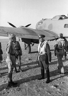 four men in military uniforms standing in front of a propeller driven aircraft