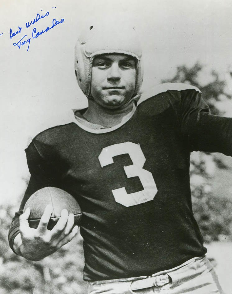 A black and white portrait of Canadeo in his football uniform and holding a football. The photo is signed by Canadeo.