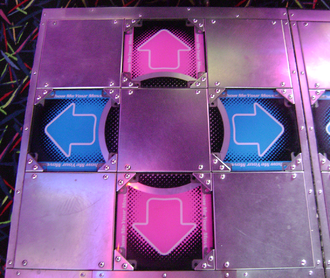 Dance Dance Revolution - The dance stage, divided into 9 sections, 4 of them in the cardinal directions contain pressure sensors for the detection of steps.