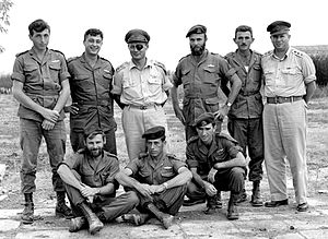 Paratroopers Brigade - Members of 890th Paratroop Battalion after Operation Egged (November 1955). Standing l to r:  Lt. Meir Har-Zion, Maj. Arik Sharon, Lt. Gen Moshe Dayan, Capt. Dani Matt, Lt. Moshe Efron, Maj. Gen Asaf Simchoni; On ground, l to r: Capt. Aharon Davidi, Lt. Ya'akov Ya'akov, Capt. Raful Eitan