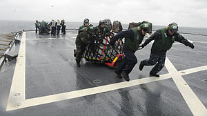 Defense.gov News Photo 120305-N-XG305-068 - U.S. Navy sailors assigned to Helicopter Anti-Submarine Squadron Light 51 move pallets off the flight deck of the U.S. 7th Fleet command ship USS.jpg