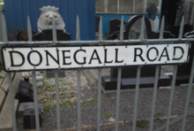 """Donegall Road"" street sign attached to metal railings."