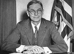 Ein Mann posiert an einem Schreibtisch.  Hinter ihm steht eine amerikanische Flagge.