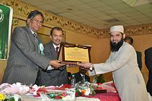 Dr. Mohammad Najeeb Qasmi receiving momento from Vice Chancellor of Jamia Millia Islami, New Delhi on 12 December 2014 in Riyadh.jpg