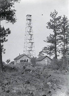 A four-legged tower with a small at the top, next to two one-story buildings. The tower is four stories tall. Trees are at either side, and in the foreground, there are rocks, some vegetation, and a rough trail.