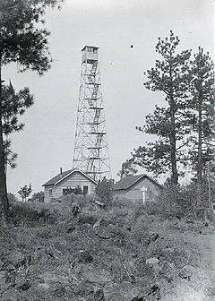 Et firbent tårn med et lite på toppen, ved siden av to enetasjes bygninger.  Tårnet er fire etasjer høyt.  Trær er på begge sider, og i forgrunnen er det steiner, noe vegetasjon og en grov sti.
