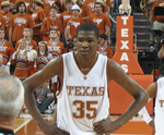 A basketball player, wearing a white jersey with the word «TEXAS» and the number 35 on the front, stands on a basketball court.