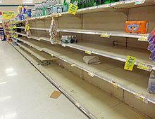 A supermarket aisle with a large section empy save for scattered packages of bottled water