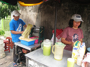Sugarcane juice - Es air tebu, iced sugarcane juice sold by street vendor in Jakarta, Indonesia.