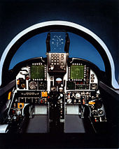 Mock-up of jet fighter's cockpit, featuring a head-up display behind windshield and displays and dials in front of the pilot.
