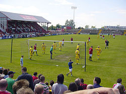 A football game in progress between F.C. United in red and Leigh Railway Mechanics Institute in yellow. The F.C. United crowd watch on.