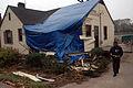 FEMA - 34856 - FEMA worker and damaged Georgia home with a blue roof.jpg