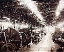 Uma fotografia que mostra o interior de uma grande fábrica edifício com iluminação fornecida pela clarabóias gerais, debaixo do qual está suspenso um eixo de linha de fornecimento de energia através de correias de polias para várias máquinas no chão de fábrica, alguns dos quais trabalhadores anão em pé por suas estações