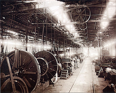 A photograph showing the interior of a large factory building with lighting provided by overhead skylights, underneath which is suspended a line shaft providing power via pulley belts to various machines on the factory floor, some of which dwarf workers standing by their stations