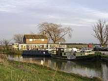 River scene of two-storey wooden building with chimney with Fish and Duck written on the front wall some canal long-boats in the foreground